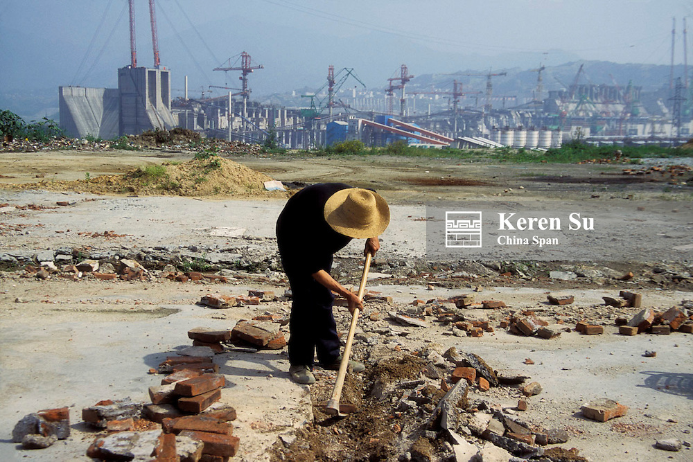 Farmer digging with construction site of Three Gorges Dam, Hubei Province, China