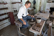 An actor portraying an 1800s potter contemplates a lump of clay as he kicks his wheel demonstration up to speed before making a cup. Conner Prairie Interactive History Park provides family-friendly fun for all ages in Fishers, Indiana, USA. Founded by pharmaceutical executive Eli Lilly in the 1930s, Conner Prairie living history museum now recreates life in Indiana in the 1800s on the White River and preserves the William Conner home (listed on the National Register of Historic Places). For licensing options, please inquire.