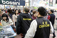 HONG  KONG, CHINA -  MARCH 17 :  Hong Kong customs agents make an arrest of counterfeit goods sales people in the Mong Kok district of Hong Kong, China on Saturday March 17, 2007.  Among the many items that were seized were handbags and watches copied from many popular manufacturers such as Rolex, Gucci, Omega and Channel.  (Photo by David Paul Morris )