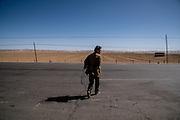 A man crosses a highway holding prayer beads in Golok region, Tibet (Qinghai, China).