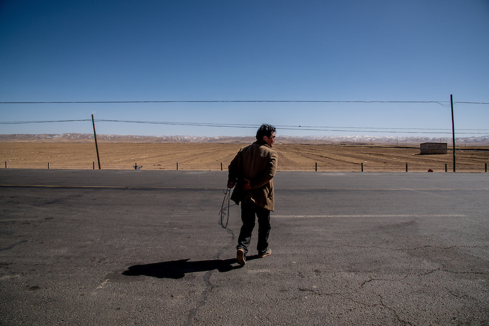 A man crosses a highway holding prayer beads in Golok region, Tibet (Qinghai, China).