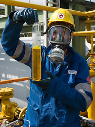 Chemist Thomas Pauwels,  holds a tube of liquid chlorine as he takes samples at the Solvay SA chemical plant in Antwerp, Belgium, on Thursday, April 22, 2010. Since the boiling point of liquid chlorine is minus 34.1 degrees Celsius, (-34.1 °C) the glass tubes containing the samples are submerged in dry ice.  Solvay SA is the world's largest supplier of Soda Ash or Sodium Carbonate and is also a major producer of caustic soda, hydrogen peroxide, chlorine and fluorinated products. (Photo © Jock Fistick)