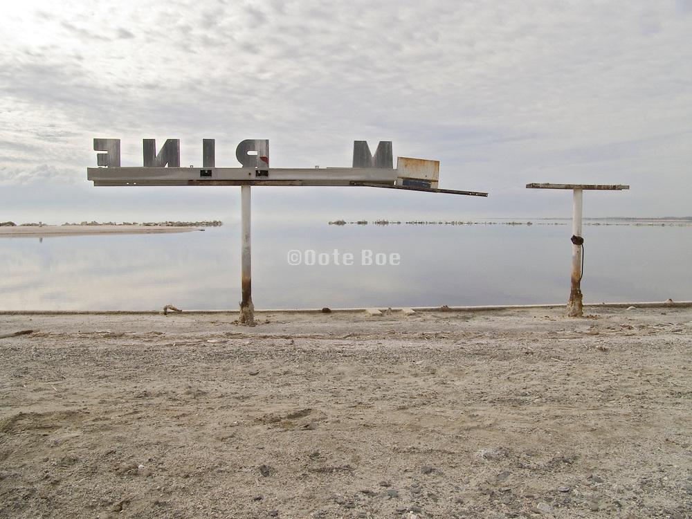 abandoned marina sign at water edge