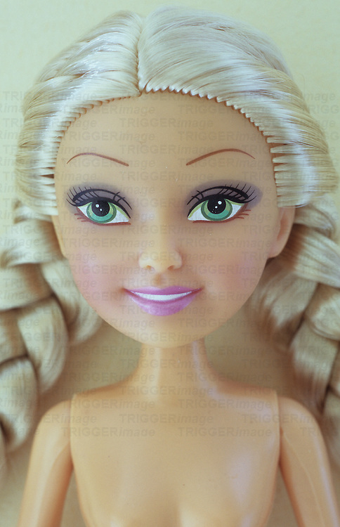 Close up of female doll with stereotypical big green eyes long plaited blonde hair