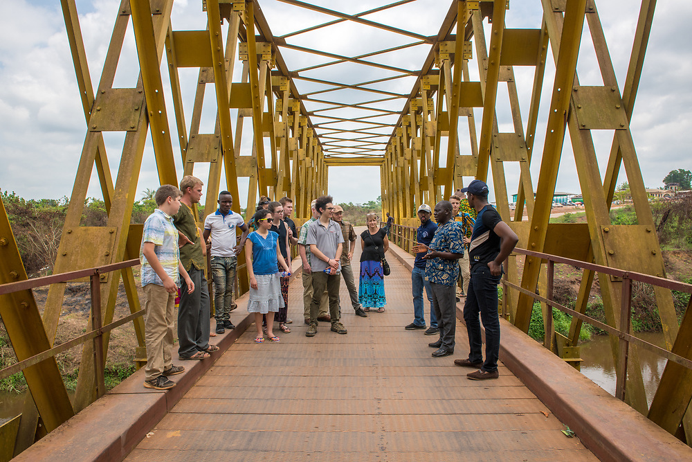 Group of student tourists gather and listen to their tour guide speak to them while standing on bridge, Republic of Guinea
