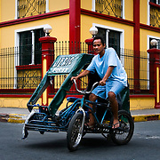 MANILA (Philippines). 2009. Tricycle in Intramuros streets. The tricycle is a little, roofed sidecard bolted to a bycicle and is one of the most popular  transports for short journeys in Manila.