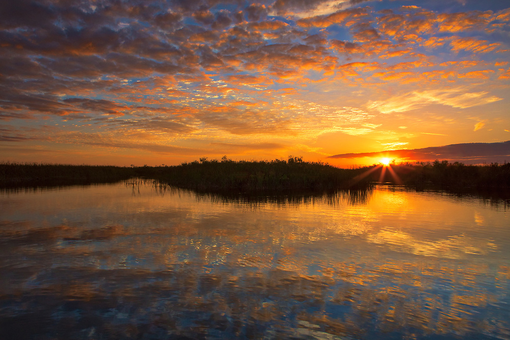 South Florida nature photography from outdoor photographer Juergen Roth showing a stunning sunset across Loxahatchee National Wildlife Refuge located west of Boynton Beach in Palm Beach County, FL. Arthur R. Marshall Loxahatchee National Wildlife Refuge is an amazing area for viewing wildlife and photography in Florida. <br /> <br /> Sunset art photos of the Arthur R. Marshall Loxahatchee National Wildlife Refuge area are available as museum quality photo prints, canvas prints, wood prints, acrylic prints or metal prints. Fine art prints may be framed and matted to the individual liking and decorating needs:<br /> <br /> https://juergen-roth.pixels.com/featured/south-florida-wetland-sunset-juergen-roth.html<br /> <br /> All digital nature photo images are available for photography image licensing at www.RothGalleries.com. Please contact me direct with any questions or request.<br /> <br /> Good light and happy photo making!<br /> <br /> My best,<br /> <br /> Juergen<br /> Prints: http://www.rothgalleries.com<br /> Photo Blog: http://whereintheworldisjuergen.blogspot.com<br /> Instagram: https://www.instagram.com/rothgalleries<br /> Twitter: https://twitter.com/naturefineart<br /> Facebook: https://www.facebook.com/naturefineart