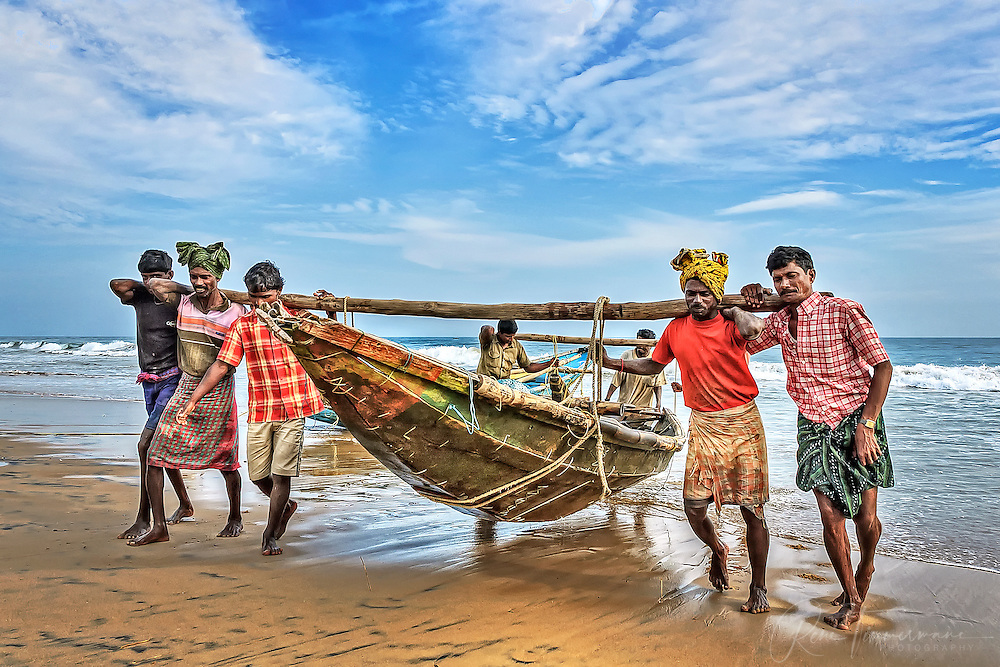 fishermen are carrying a boat