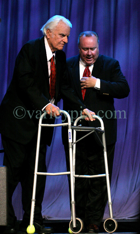 March 12th, 2006. New Orleans, Louisiana. <br /> Claiming this to be his last event preaching from the pulpit, the world's most famous evangelist, The Reverend Billy Graham is helped to the lectern as he prepares to address a capacity crowd at the New Orleans Arena as he brings his 'Celebration of Hope' weekend event to an end.<br /> Photo&copy;; Charlie Varley/varleypix.com