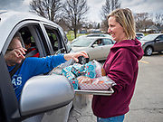 """26 MARCH 2020 - DES MOINES, IOWA: JILL BURKE, a principal at a Des Moines school, delivers hot meals to a waiting car full of students at Weeks Middle School. Des Moines Public Schools (DMPS) started distributing hot lunches Thursday, the first day students were supposed to return to school. Schools will now remain closed until 13 April. Meals were distributed with """"social distancing"""" in mind. On Thursday morning, 24 March, Iowa reported 175 confirmed cases of the Coronavirus (SARS-CoV-2) and COVID-19. Restaurants, bars, movie theaters, places that draw crowds are closed until 07 April. The Governor has not ordered """"shelter in place""""  but several Mayors, including the Mayor of Des Moines, have asked residents to stay in their homes for all but the essential needs. People are being encouraged to practice """"social distancing"""" and many businesses are requiring or encouraging employees to telecommute.         PHOTO BY JACK KURTZ"""