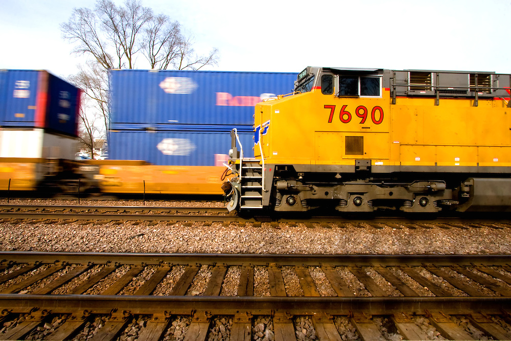 A fast moving intermodal train passes a stopped train.