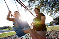 Anisha Ortiz, 17, pushes her friend's daughter Tamara Chapa, 3, on the park swing set Wednesday, Jan. 4, 2012 as the high school senior talks about why she stopped going to school. Ortiz, who is 2 months pregnant, said she couldn't learn anymore at Premont High School, and plans to get her GED. Low attendance rates are one major factors in the Texas Education Agency's decision to shut the district down.