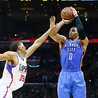 21 December 2015: Oklahoma City Thunder guard Russell Westbrook (0) takes a jump shot over Los Angeles Clippers forward Wesley Johnson (33) during the Oklahoma City Thunder 100-99 victory over the Los Angeles Clippers, at the Staples Center, Los Angeles, California, USA.