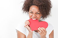 Portrait of frustrated young African American woman biting heart shape against white background