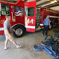 Shannon Volunteer Firemen Chris Estes, left, and Jamey Burrow get ready to clean fire hoses used in a Tuesday house fire and then put them back on the stations new truck.