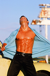 man opening up his shirt and showing off his muscular body outdoors