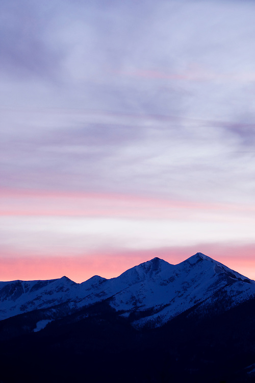 Snowy mountain ridge silhouetted by beautiful sunset.