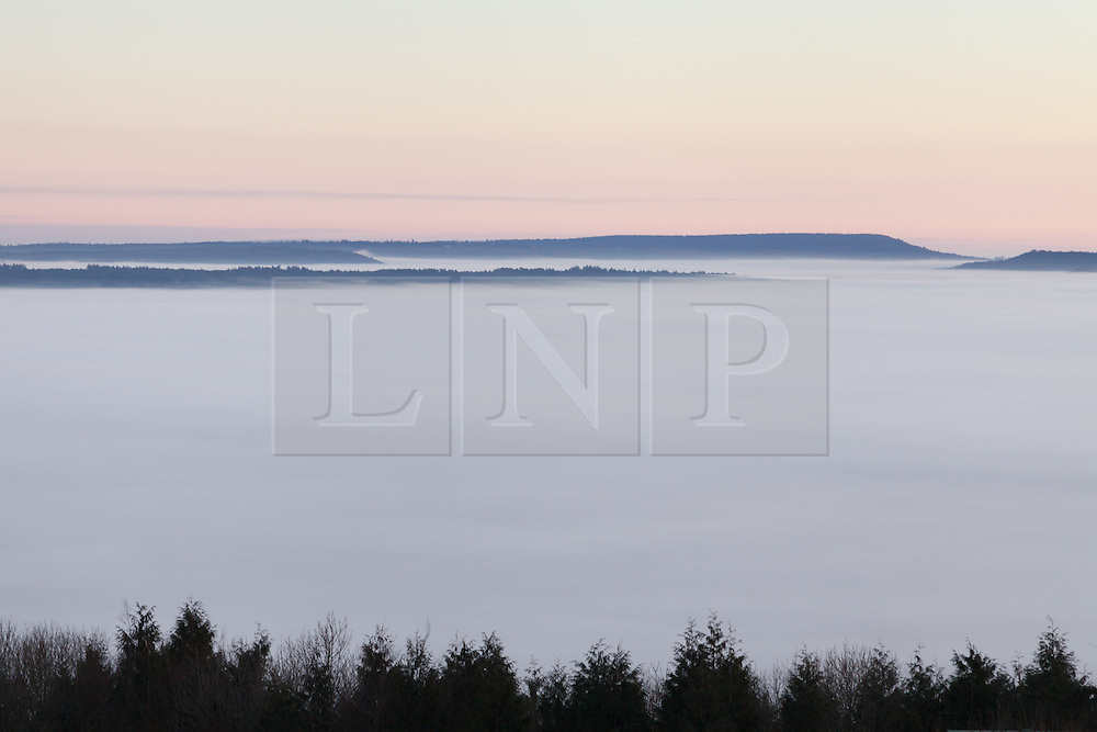 © Licensed to London News Pictures. 21/01/2014. Butser Hill, Petersfield, Hampshire, UK. Hills peeking through the low cloud revealed during sunrise in Hampshire this morning, 21st January 2014. Photo credit : Rob Arnold/LNP