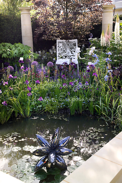Urban garden with pond, prismatic sculpture 'Rocket Pollen' by Rebecca Newnham, flowering perennial bed including Allium 'Beau Regard', Verbascum 'Helen Johnson', Eremurus, Iris 'Superstition', Iris 'White City', Iris chrysogrpahes, Iris sibirica 'Tropic Night' &amp; Iris 'Jane Philips' &amp; Salvia 'Rhapsody in Blue'. Ornamental trees include Fagus sylvatica Rohanii, Kalopanax &amp; Viburunum plicatum Mariesii. Metal chair &amp; stone classical columns.<br /> Dawn Chorus sponsored by Bradstone.Design by Chris Beardshaw. The Chris Beardshaw Mentoring Scholarship Team. Silver-Gilt Flora medal winner