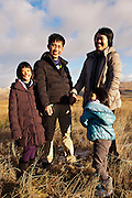 Asian man and woman with two children aged 9 and 7 hold hands smiling in the Moffat Hills.