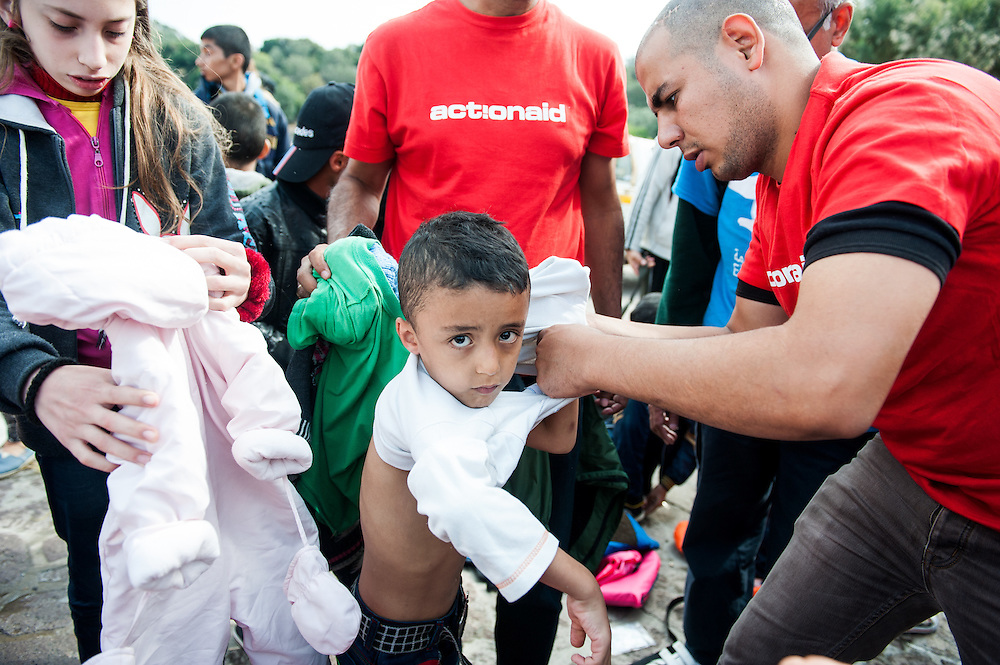 ActionAid's translator Moustafa helps Ali from Aleppo, Syria to take off his wet clothes at the fishing harbour of Skala Sykamias, Lesvos, Greece.