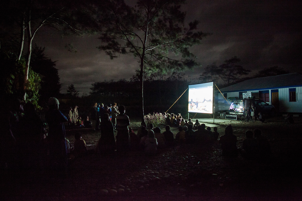 Children and parents from the Husoak village outside of Wamena watch an educational movie on HIV/AIDS.  The film uses the local dialects and also entertaining and informative attracting hundreds of villagers to the showings.