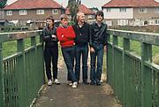 Four teenagers stand on a bridge, Perivale Park, Greenford, West London, UK, 1980s.