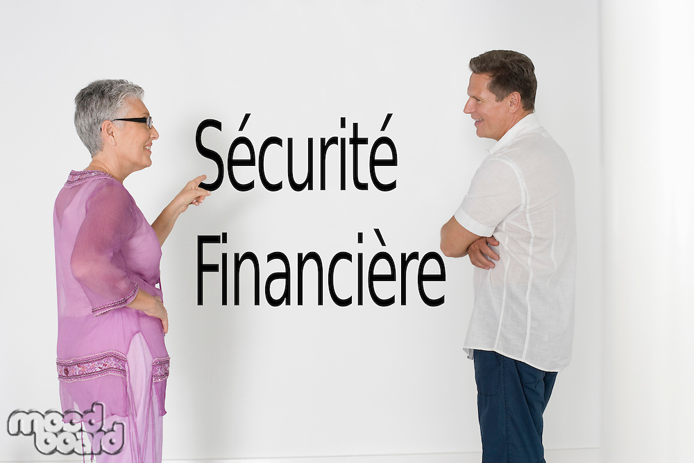 Couple discussing financial security against white wall with French text