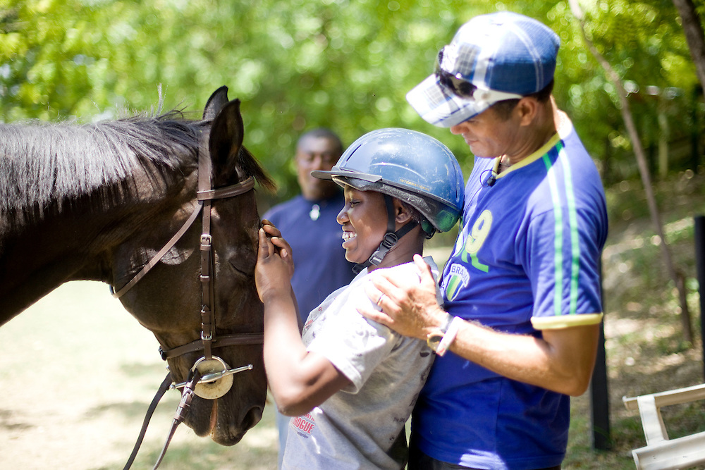 Vivian Michel, age 18  (all the chilren's last names are Michel because that is the name of the orphanage director) rides a horse during an equestrian therapy session with Athletic Club Centre Equestre manager Paco Gonzales. For two years Gonzales has been doing equestrian therapy with young people with disabilities from the Wings of Hope orphanage in Fermathe. Gonzales, formally a professional horse jumper, was inspired to start doing equestrian therapy after an accident left him unable to walk for two years. Gonzales says the children have been transformed by the horse riding and some have become more emotionally stable. One of the children, Vivian Michel, has improved her ability to walk. All of the children have learned how to ride.