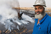 Aisa Bou Yabes, head of the Kuwait Oil Company firefighting team dispatched to southern Iraq smiles ever so slightly after his team extinguished their first oil well fire in Iraq's Rumaila field. The wells were set on fire with explosives by retreating Iraqi troops when the US and UK invasion began. Seven or eight wells were set ablaze. Here the ground is still smoking and oil boiling as the well still spurts some oil. The Rumaila field is one of Iraq's biggest oil fields with five billion barrels in reserve. The burning wells in the Rumaila Field were ignited by retreating Iraqi troops when the US and UK invasion began in March 2003. Rumaila is also spelled Rumeilah.