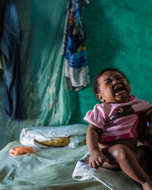 Georgine, age two months, cries as she is held by her mother on Monday, December 15, 2014 in the Carrefour area of Port-au-Prince, Haiti.