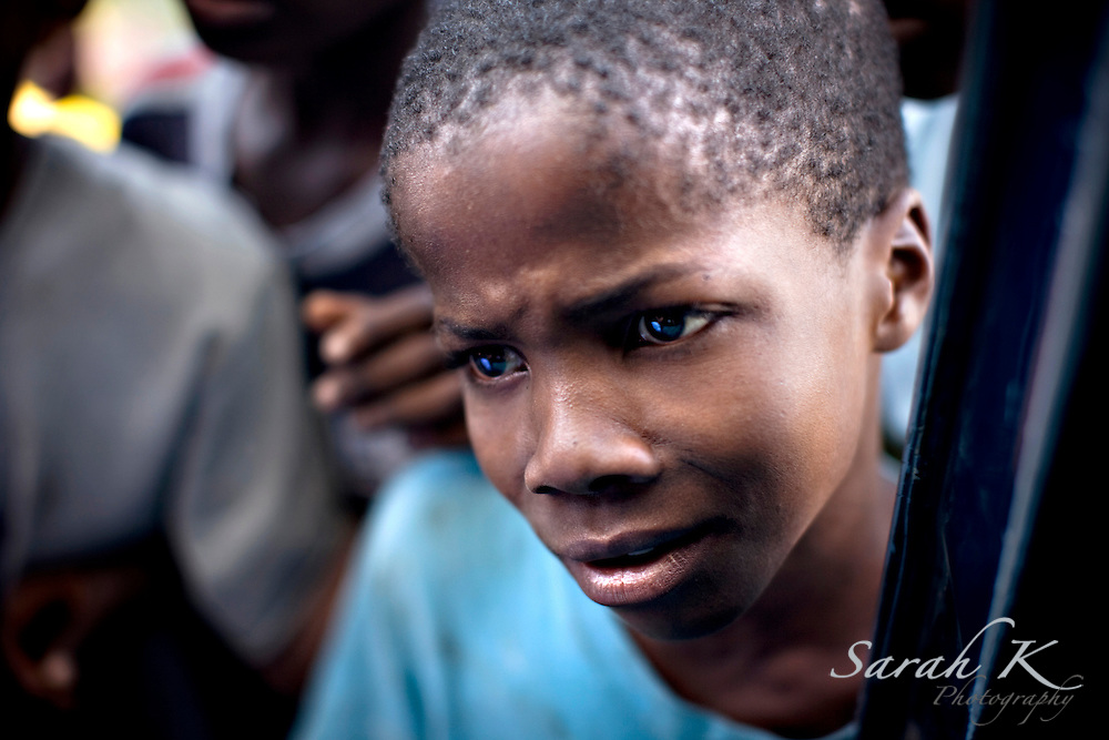 A boy begs for food from a car window in Port-au-Prince, Haiti. Many children in Haiti attempt to stay alive by begging.