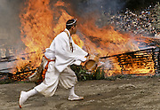 A Yamabushi or mountain priest  throws water on a large bonfire of ceder branches he will later walk across in the Hi Watari, fire walking, festival of Takao san Guchi near Tokyo, Japan. Sunday March 11th 2007