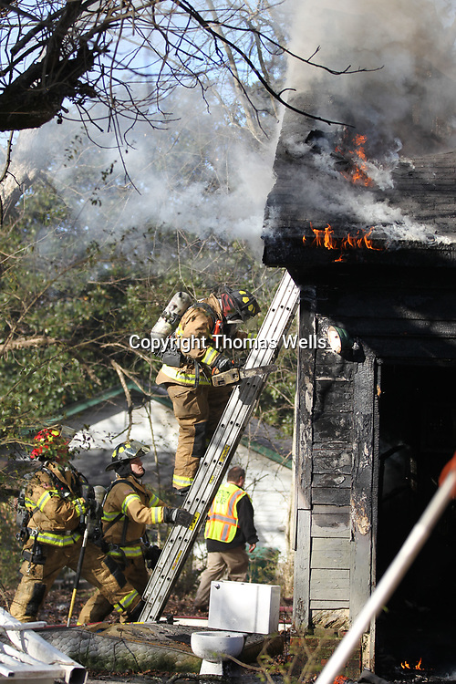 Firefighters move to the rear of the house on Walker Stret in an ateemot to put out the house fire.
