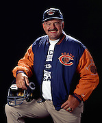 Former Chicago Bears linebacker and member of the Pro Football Hall of Fame Dick Butkus smiles as he poses for a photograph wearing an NFL Chicago Bears Throwbacks jacket and hat while holding a Bears throwbacks helmet July 8, 1993 in Los Angeles. (©Paul Anthony Spinelli)