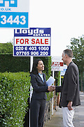 Real estate agent shaking hands with man beside for sale signs