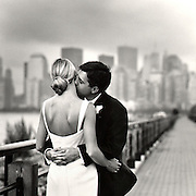 Moody B&W romantic photo of groom kissing brides neck with Manhattan NYC skyline in background