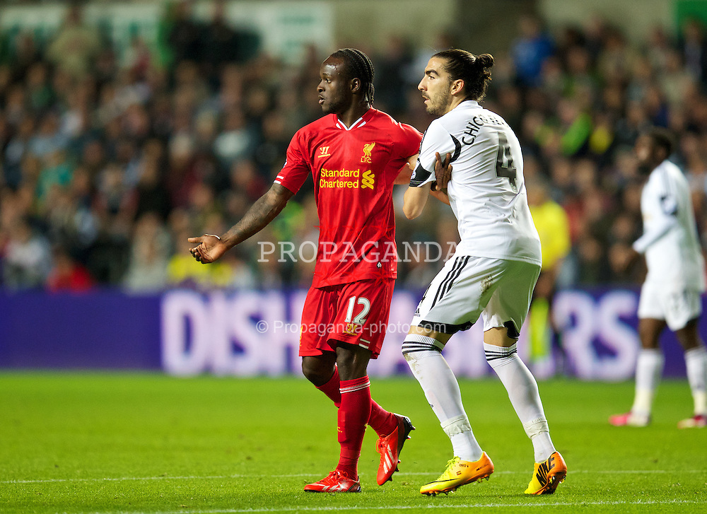 SWANSEA, WALES - Monday, September 16, 2013: Liverpool's Victor Moses in action against Swansea City's Chico Flores during the Premiership match at the Liberty Stadium. (Pic by David Rawcliffe/Propaganda)