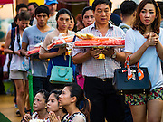21 NOVEMBER 2015 - BANGKOK, THAILAND: Women pray at the Wat Saket temple fair. Wat Saket is on a man-made hill in the historic section of Bangkok. The temple has golden spire that is 260 feet high which was the highest point in Bangkok for more than 100 years. The temple construction began in the 1800s in the reign of King Rama III and was completed in the reign of King Rama IV. The annual temple fair is held on the 12th lunar month, for nine days around the November full moon. During the fair a red cloth (reminiscent of a monk's robe) is placed around the Golden Mount while the temple grounds hosts Thai traditional theatre, food stalls and traditional shows.     PHOTO BY JACK KURTZ