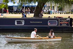 "© Licensed to London News Pictures. 24/07/2013. Stratford upon Avon, Warwickshire, UK. As temperatures rise after the recent thunderstorms and rain, people flocked to Stratford upon Avon to start enjoying the sun. Boaters on the water pass a barge called ""Transcendence"". Photo credit : Dave Warren/LNP"