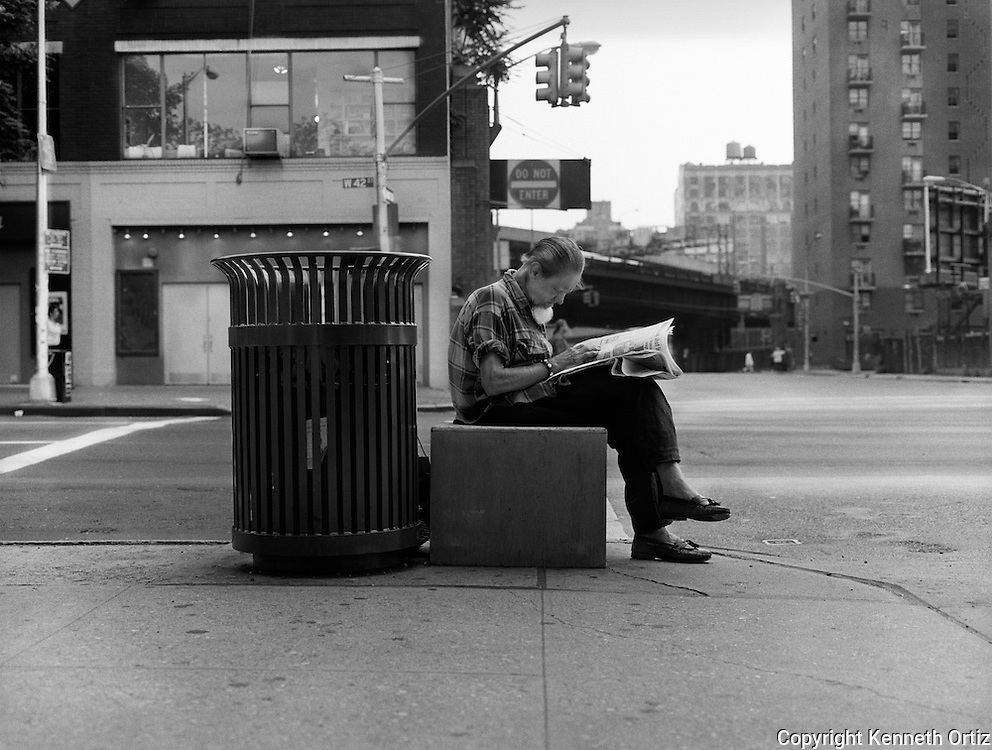 Among the the hustle and bustle of New York City, a man takes the time out to relax on a box and read his newspaper.