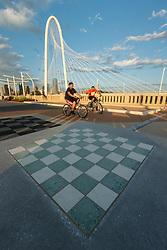 Boys on bikes on Continental Avenue Bridge with Margaret Hunt Hill Bridge in background, Trinity River, Dallas, Texas, USA.