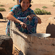 A woman cooks on an outdoor stove at her home in a village in the Karakum Desert, Turkmenistan