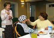 Chief executive of Agudas Israel Housing Association Itta Symons (left) talking with staff and clients while they have lunch in Schonfeld square, an Orthodox Jewish (Kosher) old peoples care home. Stamford Hill, London.