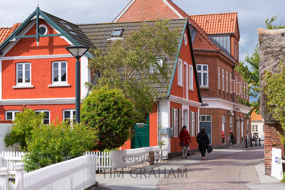 People walking past traditional thatched cottage houses on Fano Island - Fanoe - South Jutland, Denmark