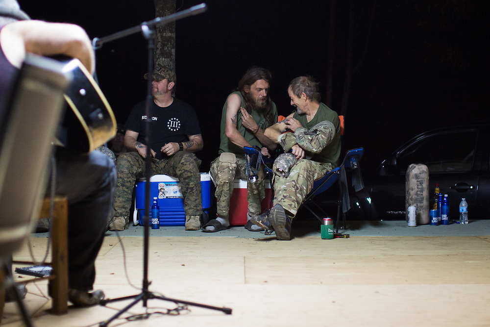 Jacob Sims (long hair), whose call sign is SK Jack and commanding officer of South Carolina Security Force III%, and Jason Thomas, whose call sign is Blackout and is a member of Georgia Security Force III%, show off tattoos to each other while listening to musician Bubba Mitchell plays following a day of training on private property near Jackson, Ga. on Saturday, April 1, 2017. Mitchell was hired to play for the event. Photo by Kevin D. Liles for BuzzFeed<br /> <br /> <br /> Shot during a FTX (field training exercises) weekend for Georgia Security Force III% militia, as well as some members for the South Carolina Security Force III%. GSF III% is part of the umbrella group, III% Security Force, which includes groups from several states. Chris Hill (Blood Agent), commanding officer of GSF III%, is the founder of the Security Force movement. According to him, GSF III% membership fluctuates between 30-50 members and growing by about one member per day.  GSF III%, as do the other groups, train one weekend per month.