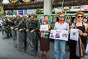 27 MAY 2014 - BANGKOK, THAILAND: Thais protesting the military coup that deposed the civilian government lined up next to soldiers during a protest in Bangkok. Several hundred people protested against the coup in Bangkok at Victory Monument. It was the fourth straight day of pro-democracy rallies in the Thai capital as the army continued to tighten its grip on Thai life. The protest Tuesday was the smallest so far.     PHOTO BY JACK KURTZ