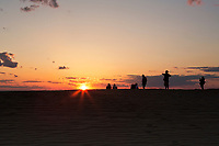 NC01431-00...NORTH CAROLINA - Watching the sunset over Roanoke Sound from a tall sand dune, a popular activity at Jockey's Ridge State Park on the Outer Banks at Nags Head.