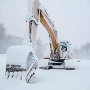 An excavation machine sites idley on a construction site during a blizzard in Wakefield, MA