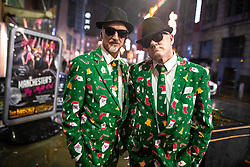 "© Licensed to London News Pictures . 21/12/2018 . Manchester , UK . Two men wear matching Christmas suits , inspired by the Blues Brothers . Revellers out in Manchester City Centre overnight during "" Mad Friday "" , named for historically being one of the busiest nights of the year for the emergency services in the UK . Photo credit : Joel Goodman/LNP"